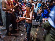 04 NOVEMBER 2014 - YANGON, MYANMAR: A Burmese Shia boy who had just whipped himself with chains on Ashura walks back to Mogul Mosque in Yangon. The flagellation shows solidarity with Hussein and his family. Ashura commemorates the death of Hussein ibn Ali, the grandson of the Prophet Muhammed, in the 7th century. Hussein ibn Ali is considered by Shia Muslims to be the third imam and the rightful successor of Muhammed. He was killed at the Battle of Karbala in 610 CE on the 10th day of Muharram, the first month of the Islamic calendar. According to Myanmar government statistics, only about 4% of the population is Muslim. Many Muslims have fled Myanmar in recent years because of violence directed against Burmese Muslims by Buddhist nationalists.    PHOTO BY JACK KURTZ