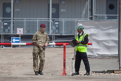 © licensed to London News Pictures. London, UK 19/07/2012. Soldier talking to a G4S security guard at the military base in Hainault Country Park in Redbridge, east London. The base will accommodate 3,000 soldiers during the Olympics. Photo credit: Tolga Akmen/LNP