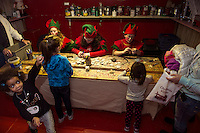 Dulce, Ella and Luna get a glimpse into Santa's Workshop with elves Nugget, Jangle and Icy during opening night of the Christmas Village on Thursday.  (Karen Bobotas/for the Laconia Daily Sun)