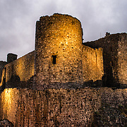 Just after the lights have been turned on at Harlech Castle in Harlech, Gwynedd, on the northwest coast of Wales next to the Irish Sea. The castle was built by Edward I in the closing decades of the 13th century as one of several castles designed to consolidate his conquest of Wales.