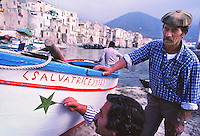 Man painting his fishing boat, in the harbor of Cefalu, Sicily, Italy