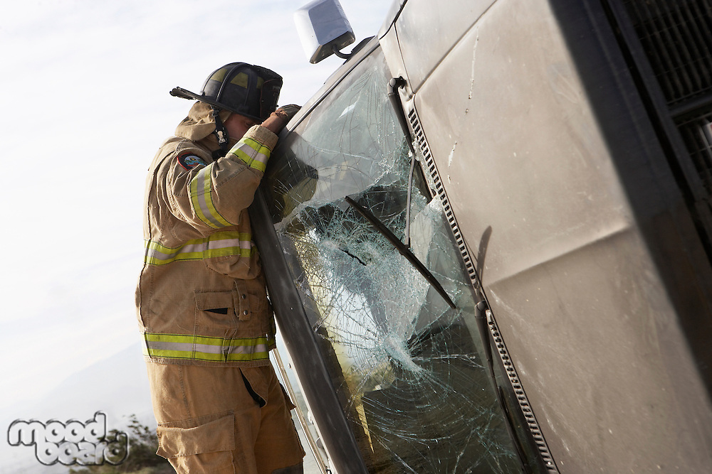Firefighter looking into crashed car