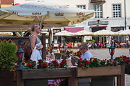 Tallinn, Estonia -- July 23, 2019. Photo takin of an outdoor cafe in Tallinn Estonia;  a man sits  at a table reading a newspaper while a standing woman is about to leave.