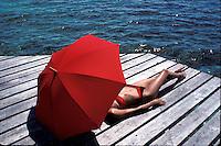 Woman in bikini sunbathing with red umbrella