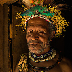 Old Huli man in front of his house with a beautiful decorated dress made of a Bird of Paradis, Tari, Papoea new Guinea.