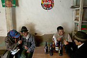 Taking advantage of their visit to town at the end of market day, men (and a few women) visit the taverns to drink Andean beer  in Simiatug, in the central Andes in Ecuador.
