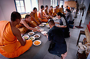 Monks eating food after a cremation ceremony at the Wat Phrabath Namphu also known as Aids Temple in Lopburi, Thailand on November 14, 2002. Family members of the deceased offer food to the monks of the temple after they have performed their ceremonial. Most of the monks at this temple are HIV positive too.