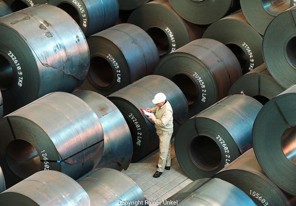 DEUTSCHLAND : Stahlproduktion bei ThyssenKrupp Stahl AG in Duisburg :.ein Arbeiter ueberprueft im Coillager der Giesswalzanlage die Warmbaender , die in sog. Coils gerollt sind ..GERMANY : Steel production at ThyssenKrupp Stahl : a worker checks  coils of steel.25.02.2003.Foto © by : Rainer UNKEL.                   Tel.: (0)228 / 477211 , Fax: (0)228 / 477212