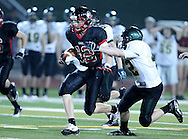 Linn-Mar's Jake Luerkens (12) tries to get away from Kennedy's Alex Boomershine (42) during the game between Cedar Rapids Kennedy and Linn-Mar at Linn-Mar Stadium in Marion on Friday evening, September 2, 2011. It was 35-7 Linn-Mar at halftime.