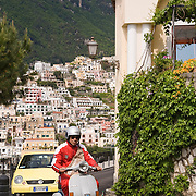 Man riding Vespa motorscooter on steep curved road in village of Positano, Italy
