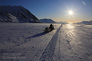 Glaciologist doing field work snowmobiles down glacier to sea at day's end; Svalbard, Norway.