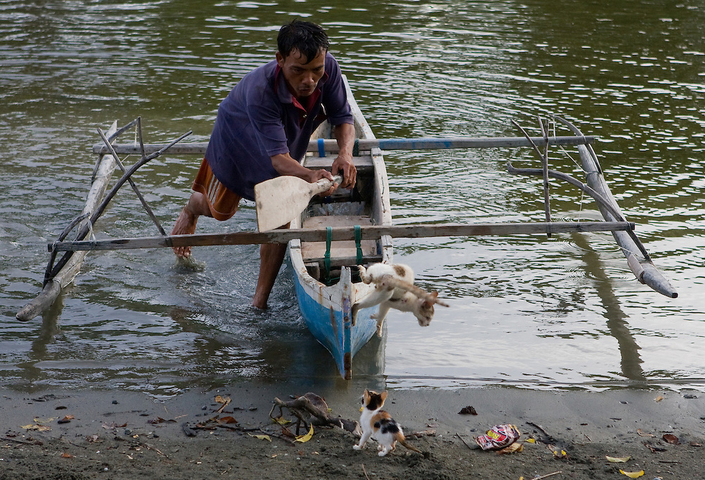 A man swats a cat off his canoe in Central Sulawesi