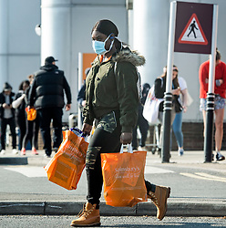 © Licensed to London News Pictures. 27/03/2020. London, UK. A woman carrying shopping bags, wearing a medical face mask, walks past large number of people queued to enter Sainsbury's supermarket on Ladbroke Grove, west London, during a lockdown over the Coronavirus spread. Prime Minister Boris Johnson has announced  that people should only leave their homes for essential work, groceries, medical necessity and exercise. Photo credit: Ben Cawthra/LNP