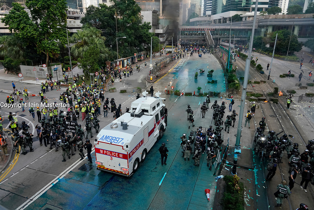 Hong Kong. 1 October 2019. After a peaceful march through Hong Kong Island by an estimated 100,000 pro democracy supporters, violent flared up at Tamar, Admiralty and moved through Wanchai district. Police used teargas and baton rounds and water cannon. Hard core group lit fires, threw bricks and Molotov cocktails at police. Violence continues into evening. Riot police advance on protestors after water cannon used. Iain Masterton/Alamy Live News.