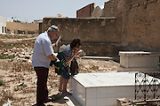 French Tunisian Jewish couple Richard and Deborah Hakoun visit the grave of their relative in the cemetery behind the Great Synagogue of the tiny Tunisian Jewish community on the island of Djerba on May 27,2016.<br /> Many Tunisian Jews that emigrated to France returned home to visit relatives during the annual pilgrimage to the ancient Ghriba synagogue .<br /> (Photo by Heidi Levine).
