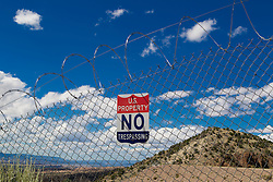 warning sign on a chain link fence in New Mexico