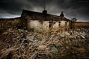 Derelict cottage sitting in open farmland near the tine cove of Porth Cwyfan at West Anglesey.