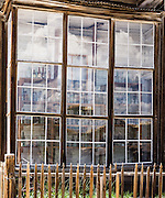 "Glass reflecting an abstract pattern of cumulus clouds obscures rows of bottles seen behind. These prominent windows front the finest home in Bodie, owned by James Stuart Cain from the 1890s - 1940s. Bodie is now California's official state gold rush ghost town. Jessie McGath originally built this house for his new wife in 1879, and JS Cain bought it in the 1890s. Cain moved to Bodie when he was 25 and built an empire starting with putting lumber barges on Mono Lake and transporting timber to support mine shafts, stoke boilers for machinery, build & heat buildings, and cook food. Cain eventually took control of the Stamp Mill though court action and went on to be the principal property owner and one of the richest men in town. Bodie State Historic Park lies in the Bodie Hills east of the Sierra Nevada mountain range in Mono County, near Bridgeport, California, USA. After W. S. Bodey's original gold discovery in 1859, profitable gold ore discoveries in 1876 and 1878 transformed ""Bodie"" from an isolated mining camp to a Wild West boomtown. By 1879, Bodie had a population of 5000-7000 people with 2000 buildings. At its peak, 65 saloons lined Main Street, which was a mile long. Bodie declined rapidly 1912-1917 and the last mine closed in 1942. Bodie became a National Historic Landmark in 1961 and Bodie State Historic Park in 1962. This image was stitched from two photos to increase pixel count and potential print size."