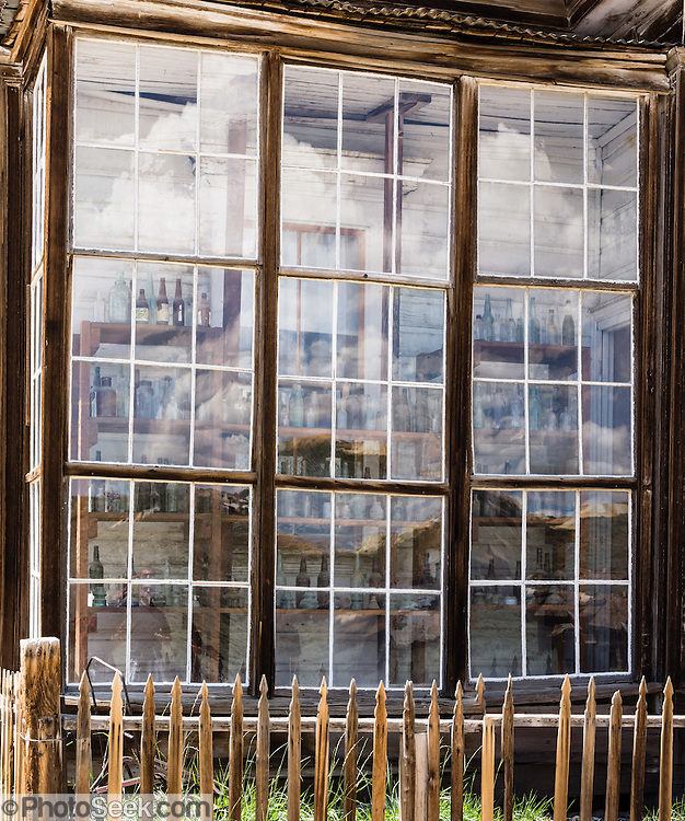 """Glass reflecting an abstract pattern of cumulus clouds obscures rows of bottles seen behind. These prominent windows front the finest home in Bodie, owned by James Stuart Cain from the 1890s - 1940s. Bodie is now California's official state gold rush ghost town. Jessie McGath originally built this house for his new wife in 1879, and JS Cain bought it in the 1890s. Cain moved to Bodie when he was 25 and built an empire starting with putting lumber barges on Mono Lake and transporting timber to support mine shafts, stoke boilers for machinery, build & heat buildings, and cook food. Cain eventually took control of the Stamp Mill though court action and went on to be the principal property owner and one of the richest men in town. Bodie State Historic Park lies in the Bodie Hills east of the Sierra Nevada mountain range in Mono County, near Bridgeport, California, USA. After W. S. Bodey's original gold discovery in 1859, profitable gold ore discoveries in 1876 and 1878 transformed """"Bodie"""" from an isolated mining camp to a Wild West boomtown. By 1879, Bodie had a population of 5000-7000 people with 2000 buildings. At its peak, 65 saloons lined Main Street, which was a mile long. Bodie declined rapidly 1912-1917 and the last mine closed in 1942. Bodie became a National Historic Landmark in 1961 and Bodie State Historic Park in 1962. This image was stitched from two photos to increase pixel count and potential print size."""