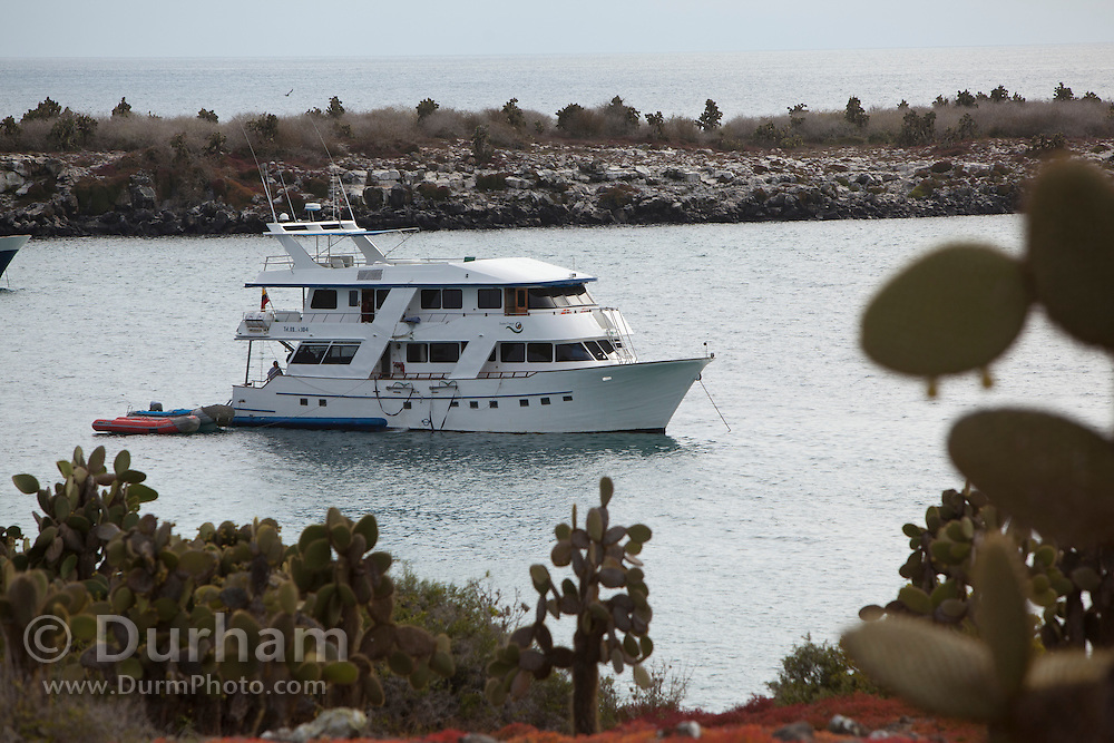 A small tour yacht taking tourists into the Galapagos islands, in this case a bay at South Plaza Island. Ecuador.