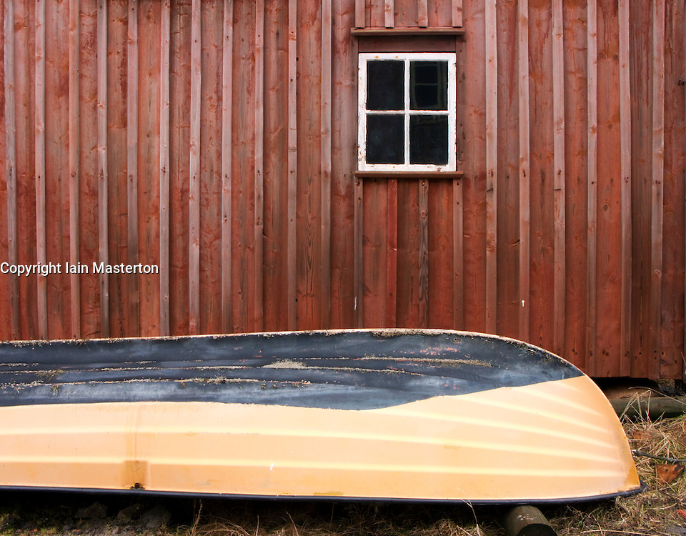 Detail of rowing boat beside traditional red timber boathouse in village of Mollosund on Bohuslan Coast of Sweden