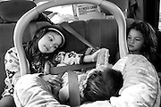 During the drive home from school, Carla feeds her baby sister Digna while her younger sister Jocelyn watches. Sept. 2012