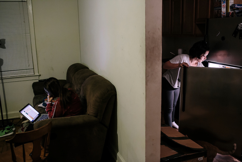 Daniela Shia-Sevilla, 15, gets dinner out of the refrigerator as her mom, Chi Shia, sits on the couch at their apartment in Fort Totten. Shia-Sevilla is an only child and spends her evenings doing homework often past midnight.