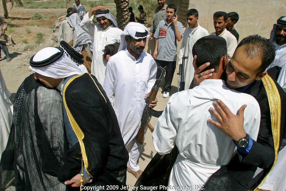 Malik Al-kasid, left in gold and black, and his son Emad Al-kasid, right in gold and black, are greeted by relatives, friends and members of different tribes for the occasion of Malik's Istikbal, or homecoming, in his home village of Suq ash Shuyukh about 20 miles southeast of Nasiriyah, Iraq, Tuesday, July 29, 2003. ..When Malik Al-kasid's caravan approached, guns were fired to announce his family's arrival. The welcming party then, returns fire to welcome him. The two parties move toward each other dancing and shooting until they join in the middle where the Hawaies occurs. ..The Al-kasid family fled Iraq after the Gulf War and their part in the uprising against Saddam Hussein in 1991, spent 3 years in Rafa, Saudi Arabia and finally settled in Dearborn, MI.The family hasn't been home to Iraq in 13 years.