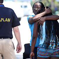 A woman comforts another Friday morning after hearing that a man suspected of shooting his girlfriend was found unresponsive at the end of a nearly three-hour standoff on West Montague Avenue in the North Charleston area. (ANDREW KNAPP/STAFF)