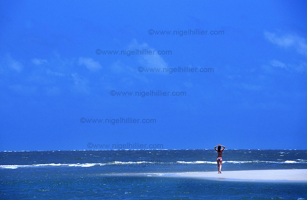 copyright: Nigel Hillier.Brazil, Para, Algodoal,girl on beach lots of blue sky and sea