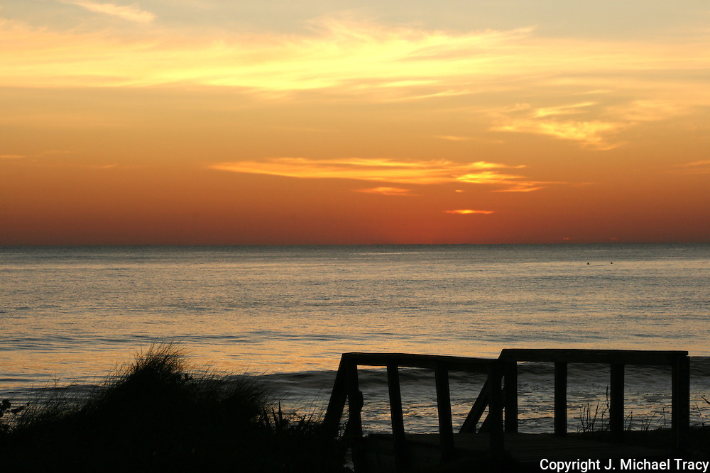 Wooden steps silhouetted against a brilliant sunrise on a Jekyll Island beach