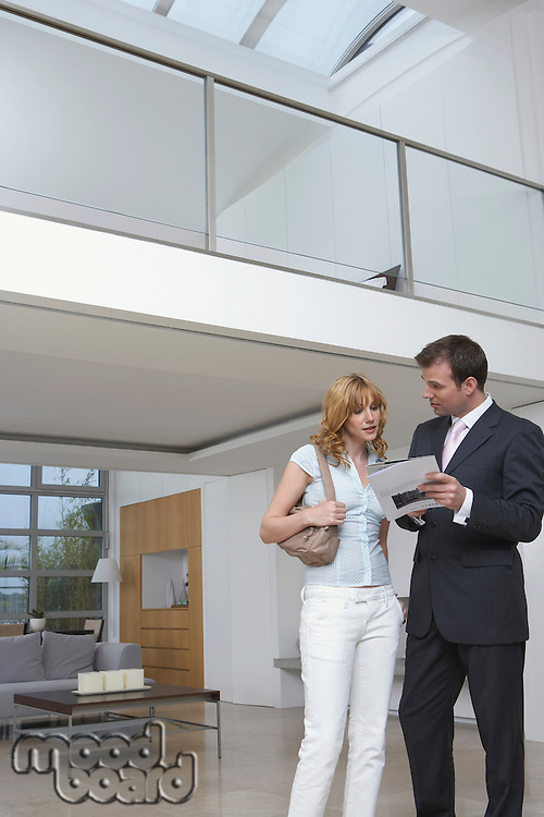 Real estate agent showing woman plan of new home