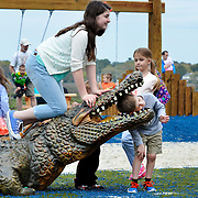 Ava Schloss, of Ohio, left, kneels on top of an alligator sculpture as her brother Augustine Scholss, right, rests his head inside of the mouth of the alligator while posing for a photo at  Shelter Cove Community Park on April 1, 2015.