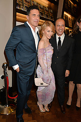 Left to right, ANDRE BALAZS, KYLIE MINOGUE and PROSPER ASSOULINE at a party to celebrate the launch of the Maison Assouline Flagship Store at 196a Piccadilly, London on 28th October 2014.  During the evening Valentino signed copies of his new book - At The Emperor's Table.