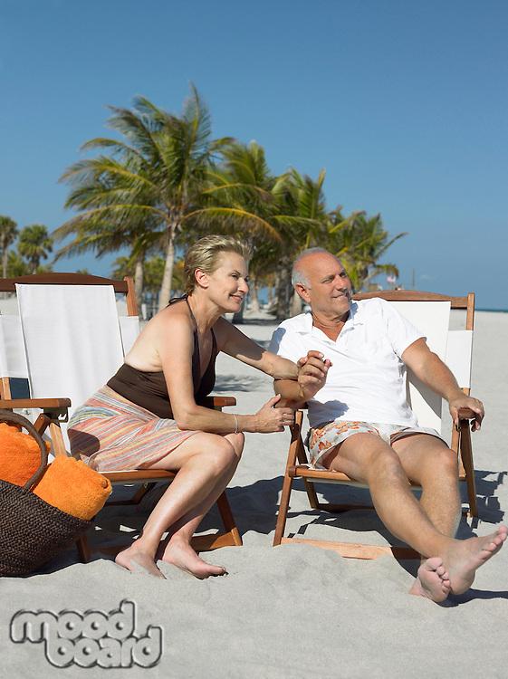 Senior couple on sunloungers on tropical beach