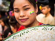 "05 APRIL 2015 - CHIANG MAI, CHIANG MAI, THAILAND: A Tai Yai woman with a Burmese flag decal on her cheek carries flower buds to throw to boys being ordained as Buddhist novices during the second day of the three day long Poi Song Long Festival in Chiang Mai. The Poi Sang Long Festival (also called Poy Sang Long) is an ordination ceremony for Tai (also and commonly called Shan, though they prefer Tai) boys in the Shan State of Myanmar (Burma) and in Shan communities in western Thailand. Most Tai boys go into the monastery as novice monks at some point between the ages of seven and fourteen. This year seven boys were ordained at the Poi Sang Long ceremony at Wat Pa Pao in Chiang Mai. Poy Song Long is Tai (Shan) for ""Festival of the Jewel (or Crystal) Sons.    PHOTO BY JACK KURTZ"