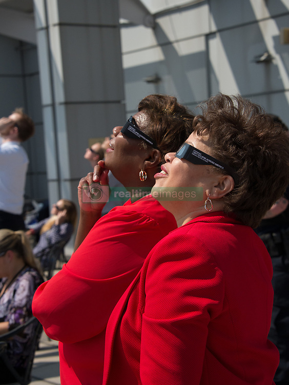 NASA employee uses protective glasses to view a partial solar eclipse from NASA Headquarters Monday, Aug. 21, 2017 in Washington, DC. A total solar eclipse swept across a narrow portion of the contiguous United States from Lincoln Beach, Oregon to Charleston, South Carolina. A partial solar eclipse was visible across the entire North American continent along with parts of South America, Africa, and Europe.  Photo Credit: (NASA/Connie Moore)
