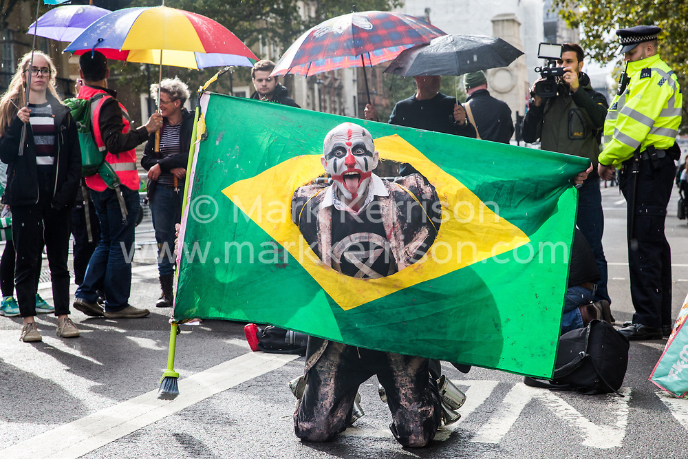 London, UK. 7 October, 2019. A Brazilian climate activist from Extinction Rebellion performs at a roadblock in Whitehall outside Downing Street on the first day of International Rebellion protests to demand a government declaration of a climate and ecological emergency, a commitment to halting biodiversity loss and net zero carbon emissions by 2025 and for the government to create and be led by the decisions of a Citizens' Assembly on climate and ecological justice.
