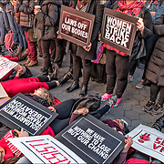 Women sit down strike at rally with signs over them.<br />