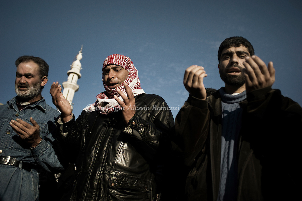 SYRIA - Homs province: Three muslim pray among hundred of people attending the funeral of five killed by a mortar attack launched by Al Asad forces, in Homs province on February 20, 2012. ALESSIO ROMENZI