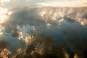 Reflection of the clouds into a lake at sunset.