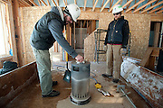 PRICE CHAMBERS / NEWS&amp;GUIDE<br /> Standing in his future living room with construction manager Dave Yogg, Jim Wolfgang heats up his lunch atop a scorching propane space heater, yielding extra-crispy results.