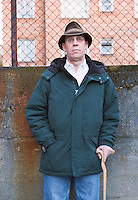 Portrait of man wearing hat and using walking cane.