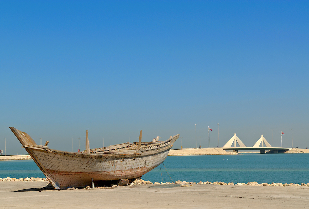 Bahrain, An old boat at the shore of Manama city infront of the Sheikh Isa Causeway Bridge