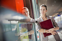 Young attractive businesswoman standing and holding document while looking through the window