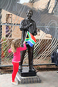 A little girl flying a South African Flag next to Mandela mural. The girl was amongst thousands of people who came from all walks of life to pay respect to the  former president Nelson Mandela outside his Houghton home, Johannesburg. Scores of people  brought flowers and lit candles in memory of the fallen hero. Mandela died on the December 5 in his Houghton home.Pic. Bafana Mahlangu. Date 05/12/2013. Sowetan