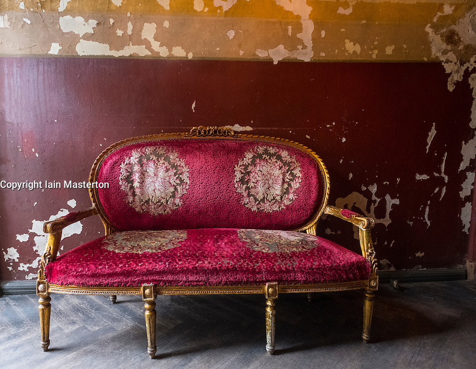Old antique red sofa with gold gilt legs and ornate decoration