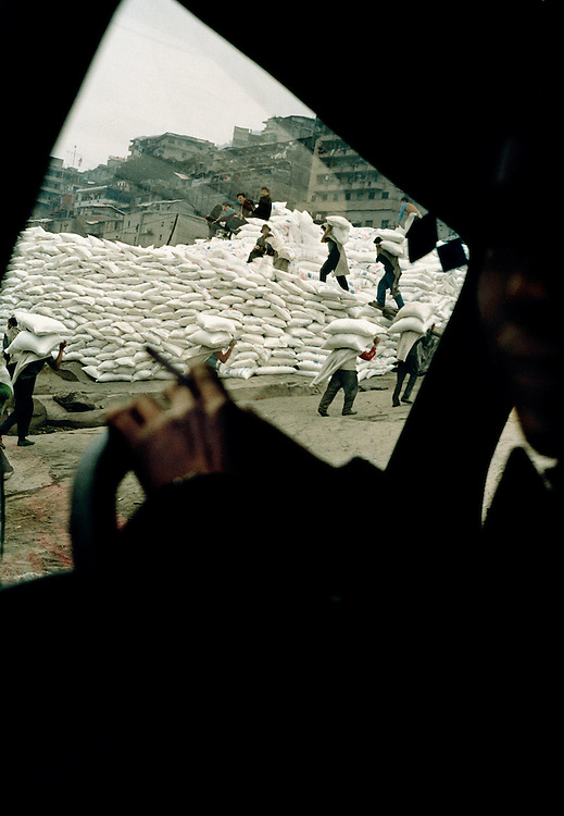 Labourers unloading sacks of salt from a nearby barge. Many of the labourers in cities and towns along the river come from surrounding villages in the hills, they flock to the larger towns for jobs and better wages. Yun Yang, China. 2000