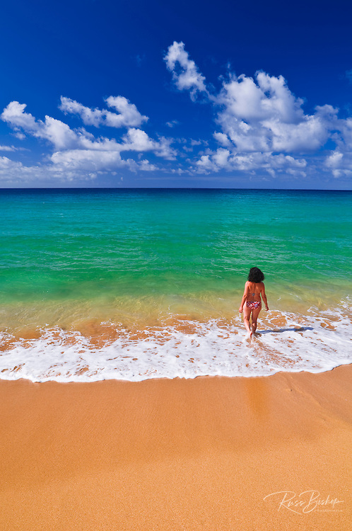 Woman enjoying the blue green waters at Secret Beach (Kauapea Beach), Island of Kauai, Hawaii