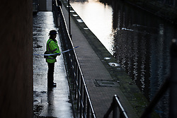 © Licensed to London News Pictures . 29/12/2013 . Manchester , UK . A PCSO stands behind police tape adjacent to the River Medlock off Oxford Road in Manchester City Centre . The search for 17 year old Adam Pickup from Stockport , who was last seen in the early hours of Saturday 28th December in Manchester City Centre following a night out with friends as , this evening (Sunday 29th December 2013), Greater Manchester Police say they have arrested two men in connection with the teenager's disappearance . Photo credit : Joel Goodman/LNP